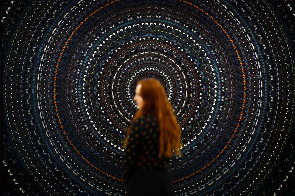 Работник галереи позирует перед новой работой Дэмиена Херста «Создатель» во время выставки в Лондоне.