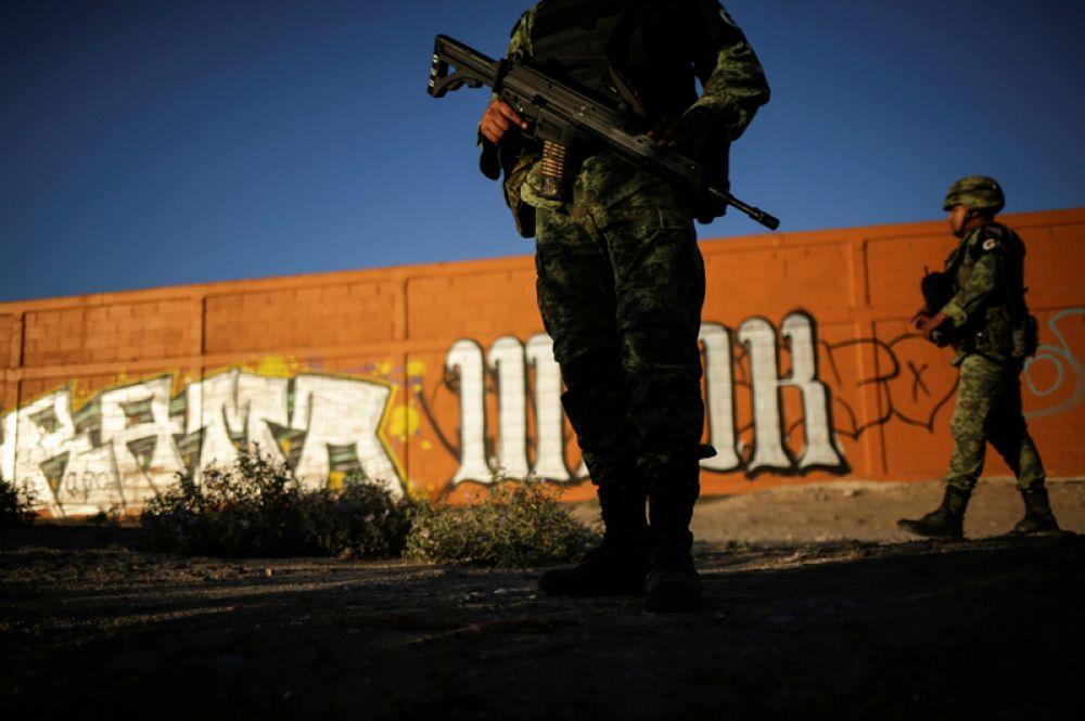 Солдаты Национальной гвардии Мексики следят за границей между Мексикой и США в районе города Сьюдад-Хуарес.