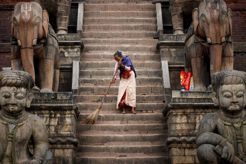 Женщина убирается в храме в Бхактапуре, Непал.