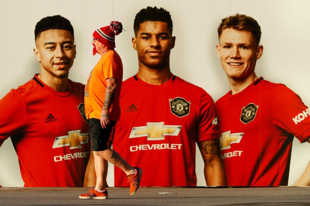 Болельщик проходит мимо плаката с изображением игроков «Манчестер Юнайтед» перед матчем Лиги Европы с «Астаной».