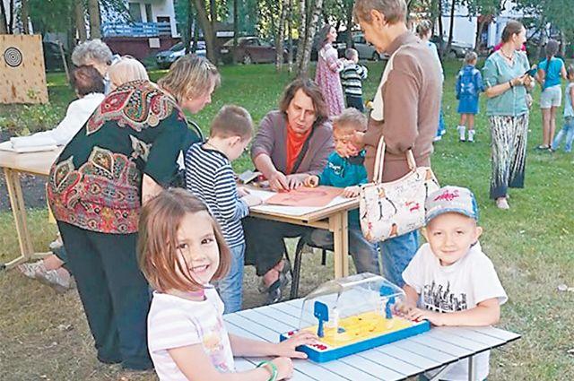 На празднике во дворе родители играли  с детьми в настольные игры.