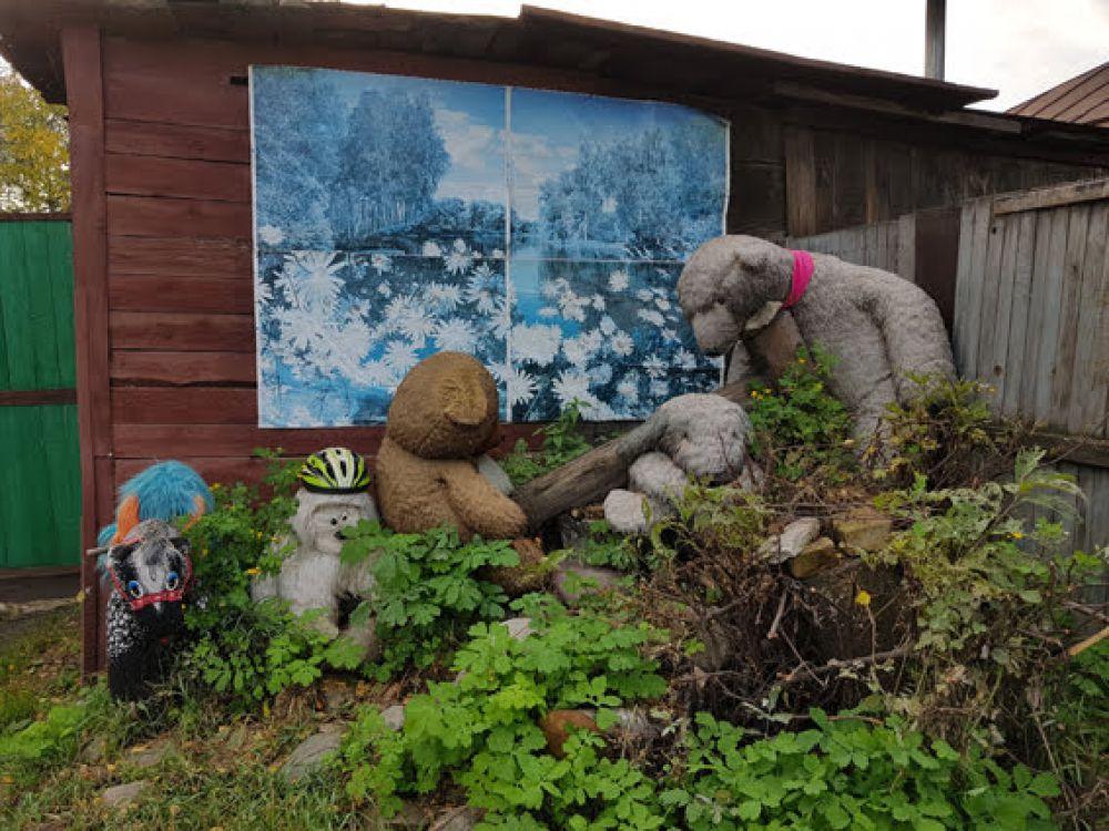 Отдельный уголок отведем плюшевым медведям: они сидят на бревне на фоне живописного пейзажа, приклееного на стенку деревянной постройки.