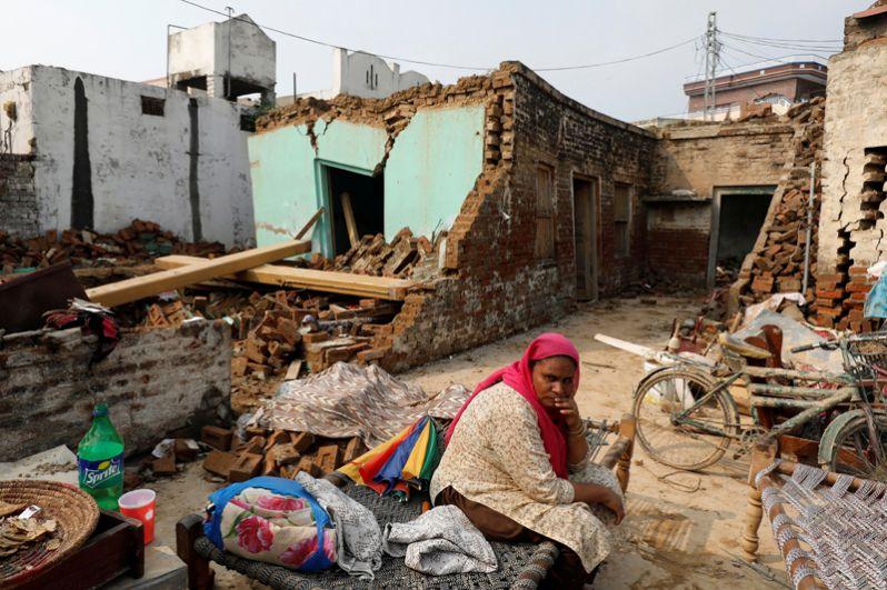 Женщина сидит рядом со своими вещами рядом с разрушенным домом после землетрясения.