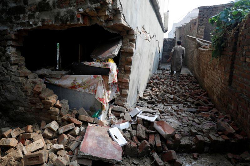 Мужчина среди руин дома после землетрясения.