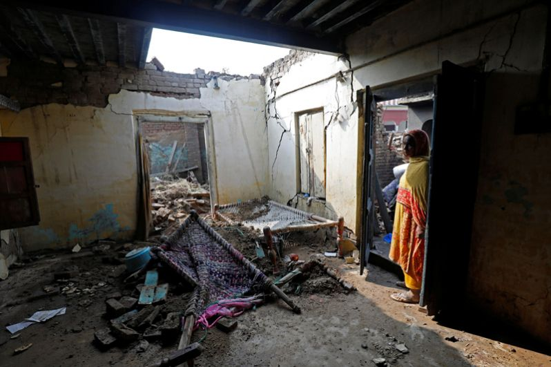 Женщина среди руин дома.