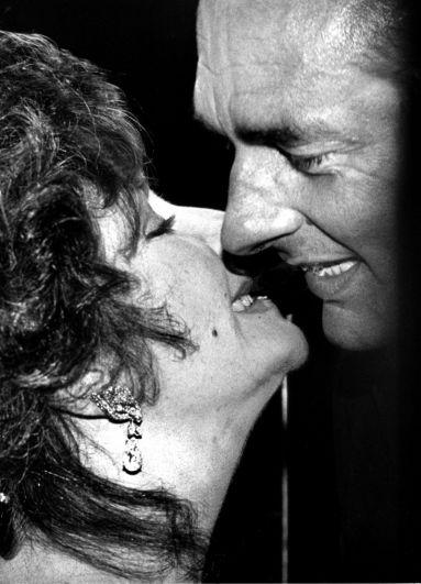 Эйлизабет Тейлор целует мэра Парижа Жака Ширака на благотворительном ужине в поддержку исследований СПИДа, 1985 год.