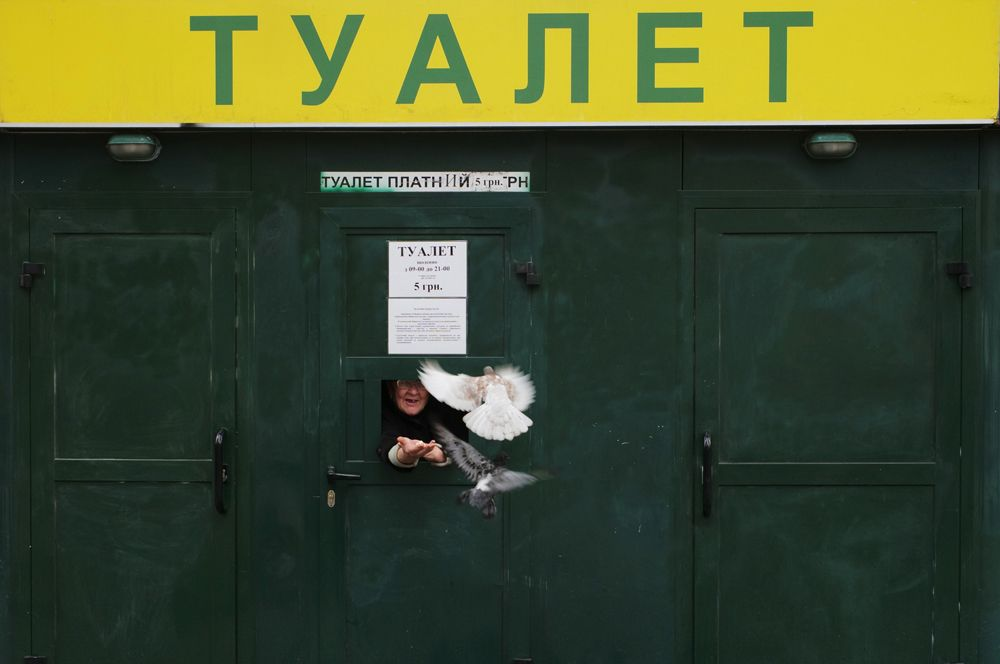 Кассир общественного туалета в центре Киева кормит голубей.