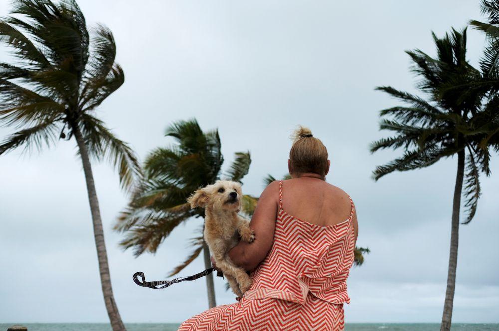 Женщина с собакой на пляже Ябукоа в Пуэрто-Рико перед приближением тропической шторма.
