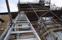 Двое строителей упали с лесов с высоты четырехэтажного дома, причем один получил травмы и попал в больницу, а другой погиб.