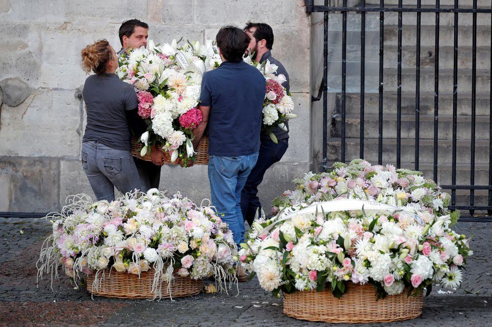 Люди несут цветы к церкви Сен-Сюльпис перед церемонией прощания с Жаком Шираком.