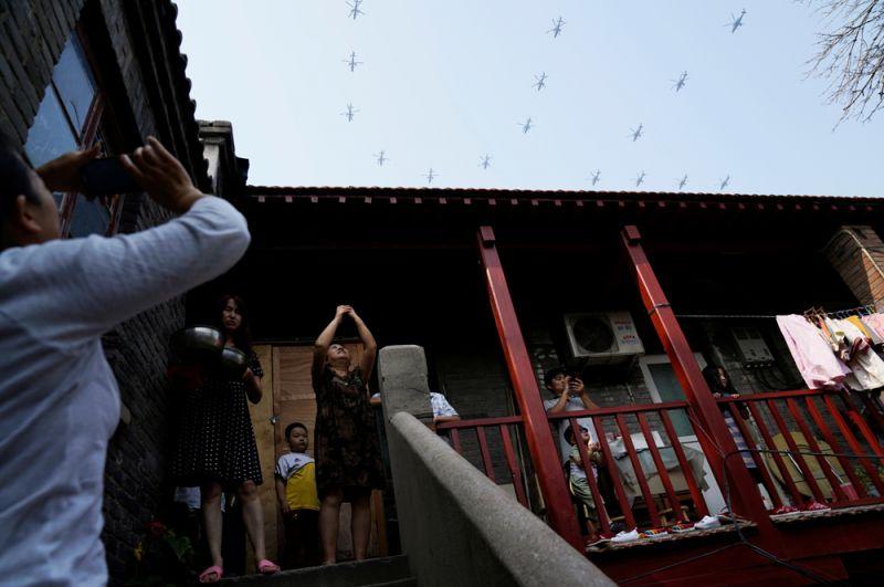 Жители наблюдают за воздушной частью парада.