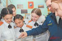 Ученики 9-го класса изучают альбом, хранящий факты из исторического прошлого Внукова, в школьном музее.