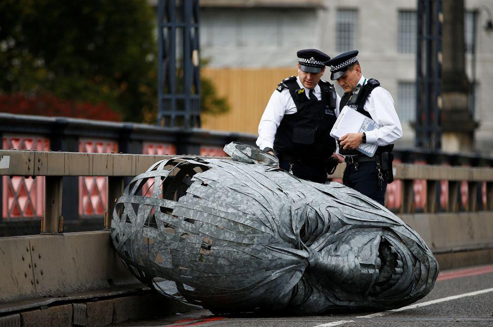 Полицейские рядом со скульптурой, сделанной активистами в Лондоне.