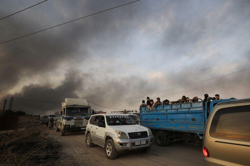 Беженцы уезжают из города Рас-эль-Айн в Сирии.