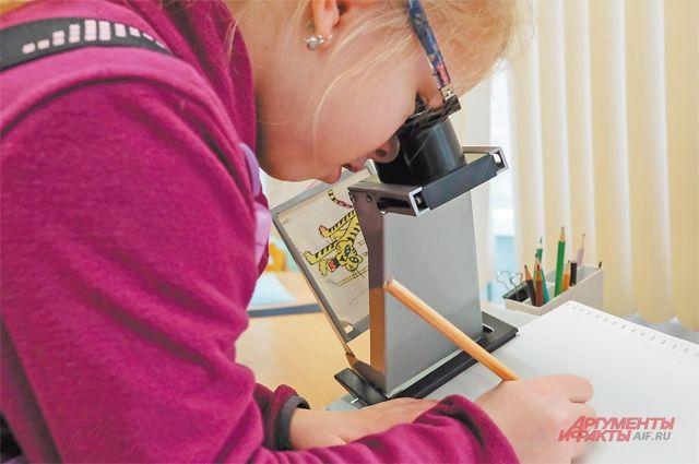 Марьяна старательно вырисовывает фигуру спомощью специального аппарата. Такими упражнениями дети занимаются доили после основных занятий подприсмотром врачей.