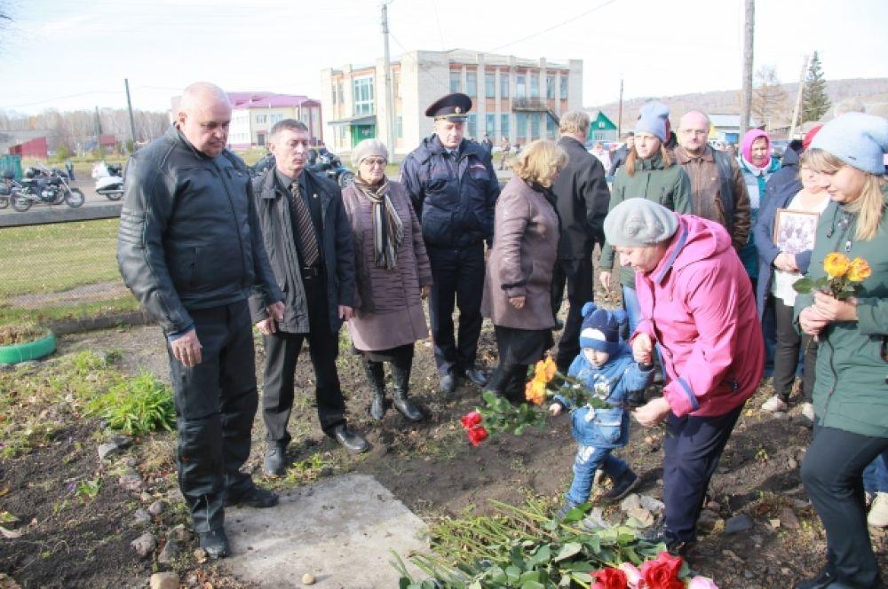 Односельчане несут цветы к дому, где родился их знаменитый земляк.