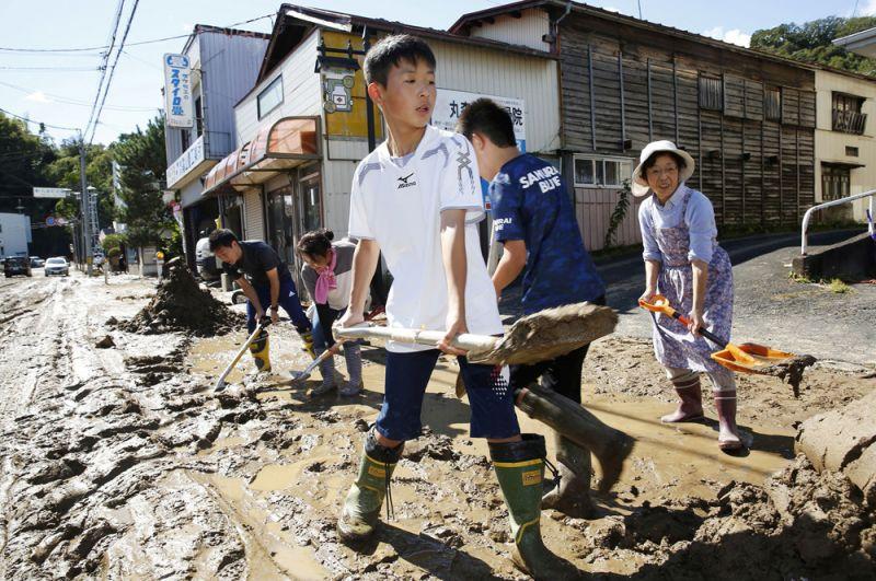 Жители поселка Марумори в префектуре Мияги убирают грязь и мусор после наводнения.