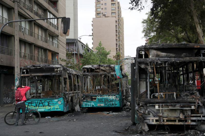 Сгоревшие автобусы, уничтоженные во время акции протеста в Сантьяго.
