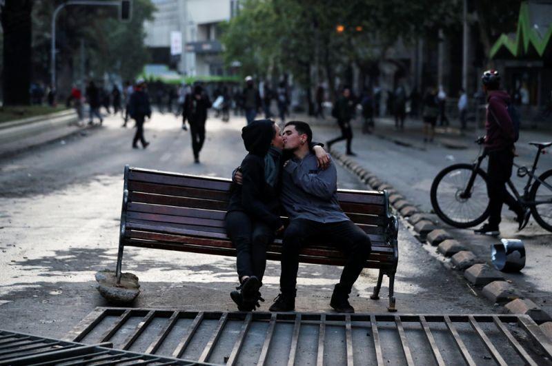 Пара на скамейке, оставленной демонстрантами во время протестов в Сантьяго.