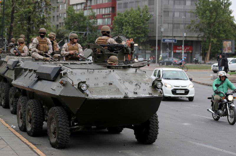 Военные на бронетранспортере патрулируют улицы Сантьяго.