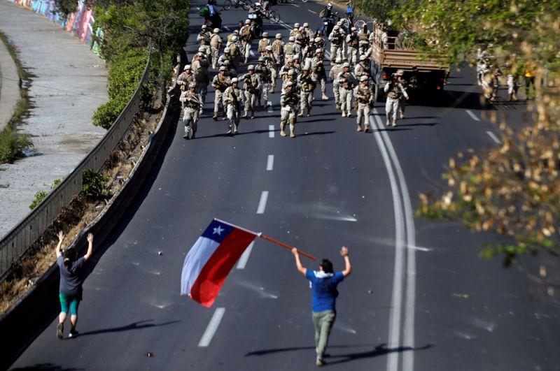 Демонстрант идет навстречу военным в Сантьяго.