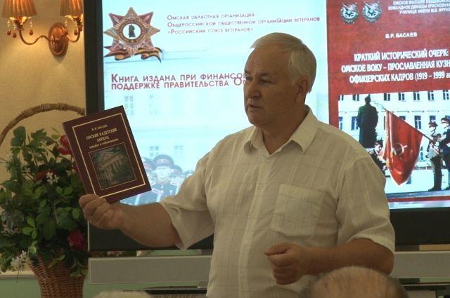 Виктор Басаев держит в руках книгу о родном училище, которую написал сам.