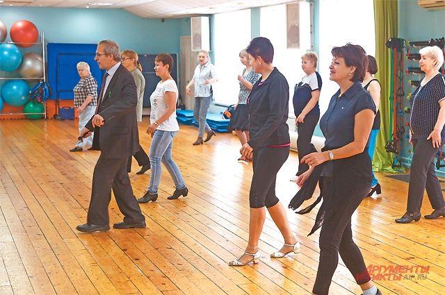 Занятия танцами начинаются сразминки. Тренер показывает движения, аучастники повторяют за ним.