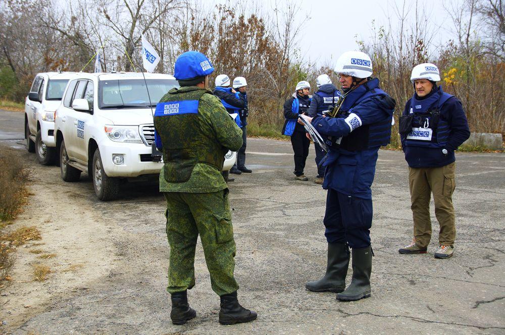 Наблюдатели ОБСЕ и члены совместного центра контроля и координации прекращения огня и стабилизации обстановки на Юго-Востоке Украины (СЦКК) в поселке Золотое в Луганской области.