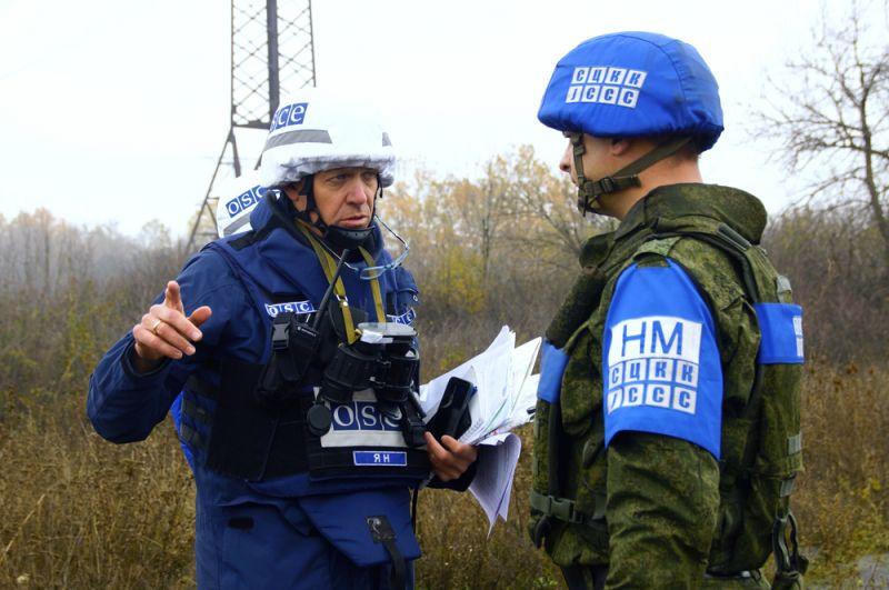 Наблюдатель ОБСЕ (слева) и член совместного центра контроля и координации прекращения огня и стабилизации обстановки на Юго-Востоке Украины (СЦКК) в поселке Золотое в Луганской области.