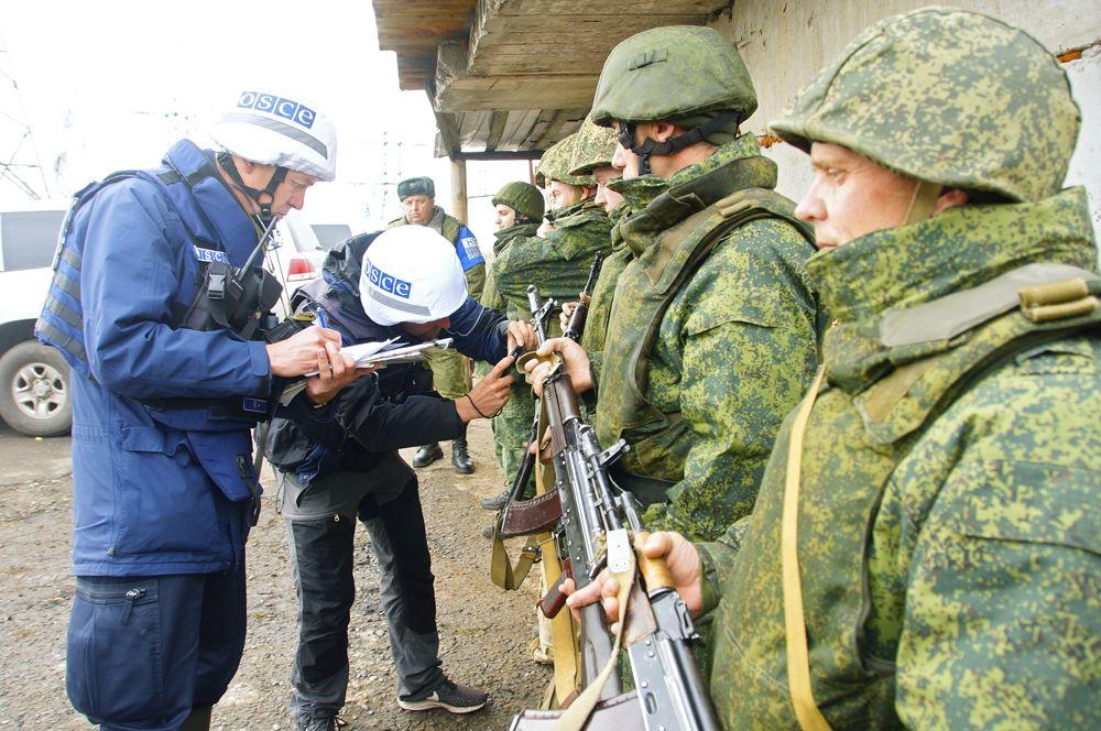 Наблюдатели ОБСЕ (слева) следят за отводом сил бойцов подразделений ЛНР в поселке Золотое в Луганской области.