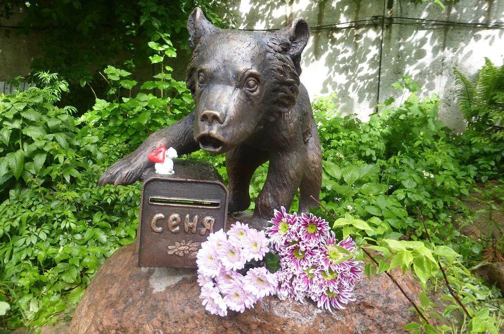 Памятник медведю Сене, Ленинградская область. В 2013 году медвежонка Сеню выкупили с притравочной станции зоозащитники. У него была диагностирована крайняя степень истощения, почти годовалый медведь весил 10 кг, отставал в росте и был похож на двух-трехмесячного. Несмотря на заботу и уход, через три года зверь скончался.