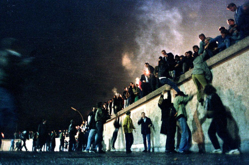 Жители Восточной и Западной Германии у Берлинской стены в районе Бранденбургских ворот.