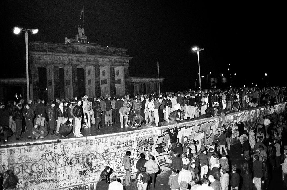 Жители Западного Берлина стоят на Берлинской стене перед Брандебургскими воротами.