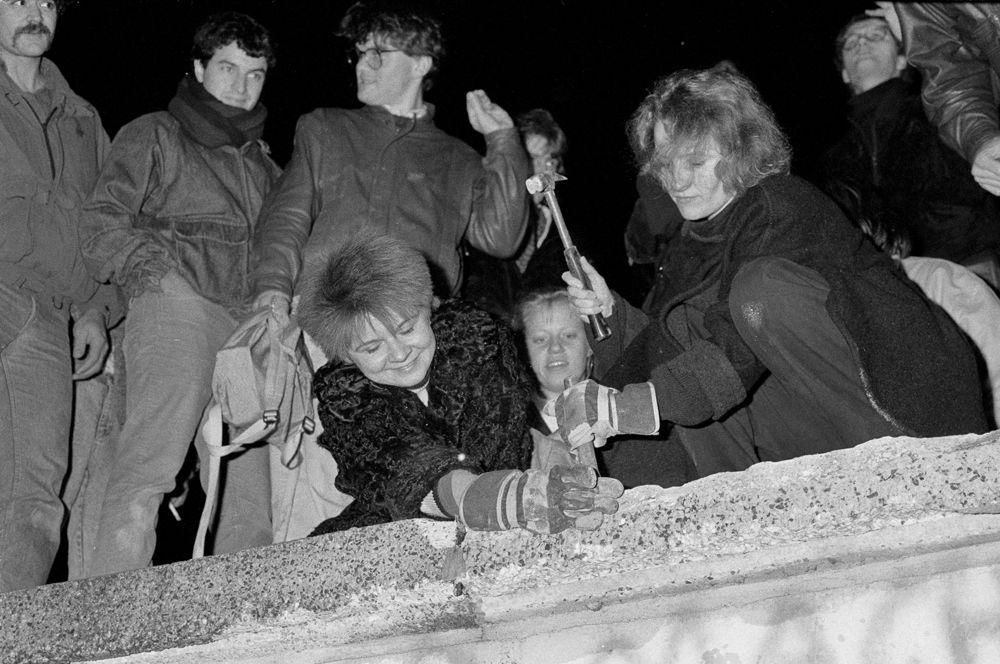 Жители Берлина с молотками и зубилами сидят на Берлинской стены в районе Бранденбургских ворот.