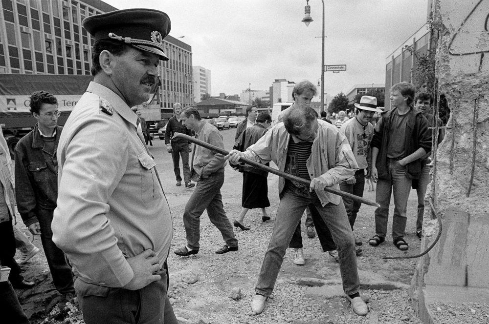Пограничник смотрит на мужчину, который откалывает кусок Берлинской стены на Руди-Дутшке-штрассе.