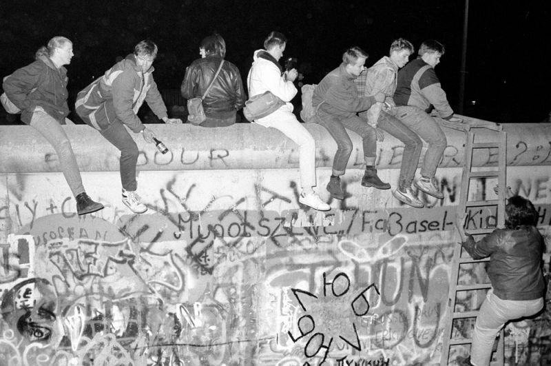 Жители Западной Германии сидят на Берлинской стене в районе Циммер-штрассе возле КПП «Чарли».
