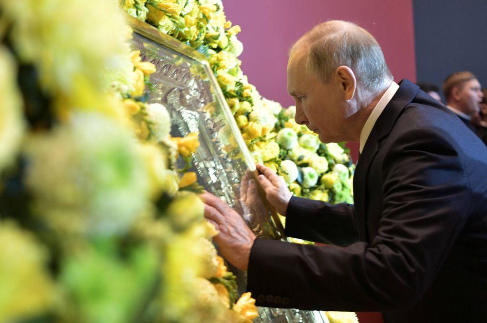 Владимир Путин прикасается к иконе во время посещения выставки «Память поколений: Великая Отечественная война в изобразительном искусстве» в День народного единства в Москве.