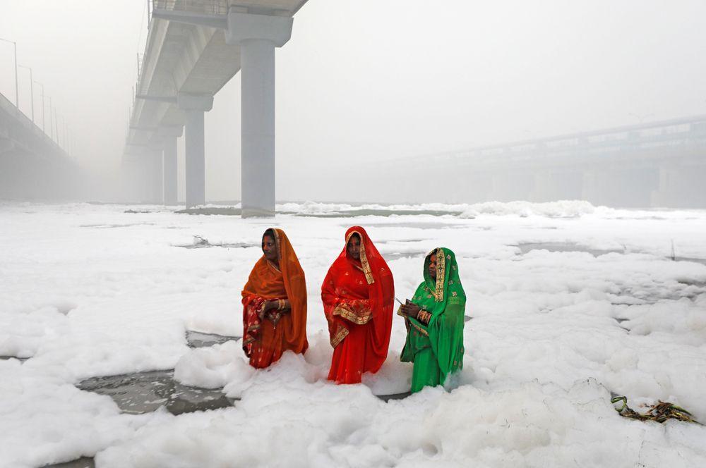 Женщины на беругу реки Джамны во время религиозного праздника Чхатх-пуджа в Нью-Дели, Индия.