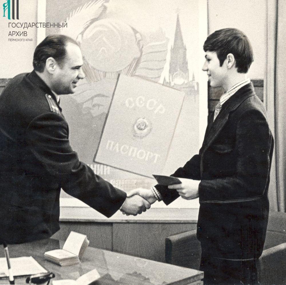 Начальник райотдела внутренних дел Мотовилихинского райисполкома, подполковник милиции В.К. Сеземин вручает паспорт отличнику учебы школьнику Роману Гришину.