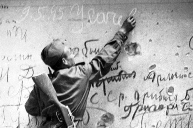 Семен Усачев делает памятную надпись на стене Рейхстага.