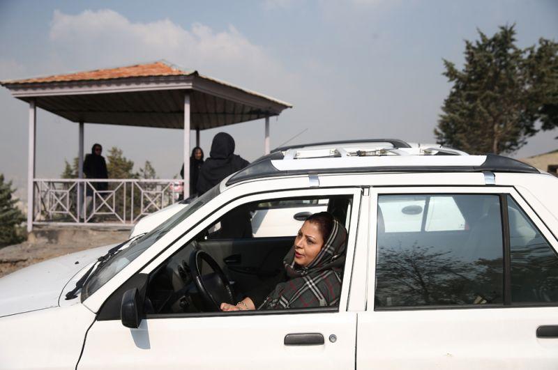 Жительница Тегерана выражает недовольство после того, как были введены квоты на розничную продажу бензина и повышены цены на топливо.