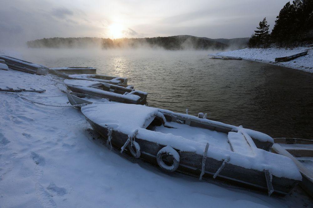 Лодки на берегу реки Енисея в таежной местности к югу от Красноярска.