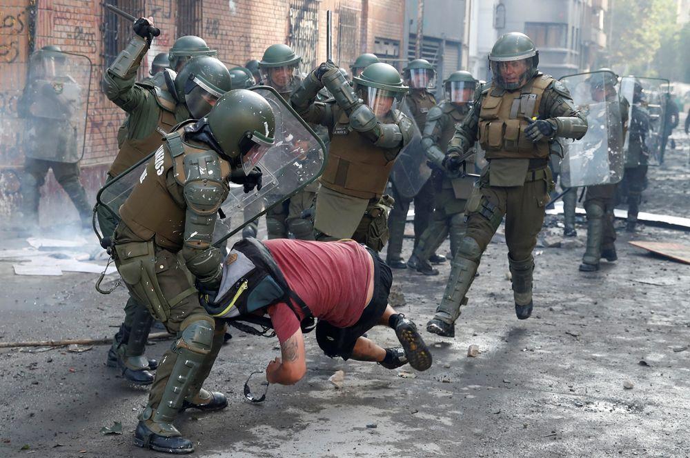 Полицейские задерживают демонстранта во время акции протеста против правительства Чили в Сантьяго.