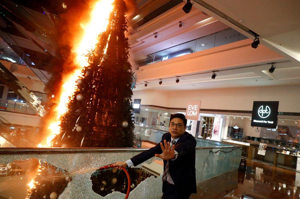 Охранник пытается погасить горящую рождественскую елку в торговом центре в Гонконге.