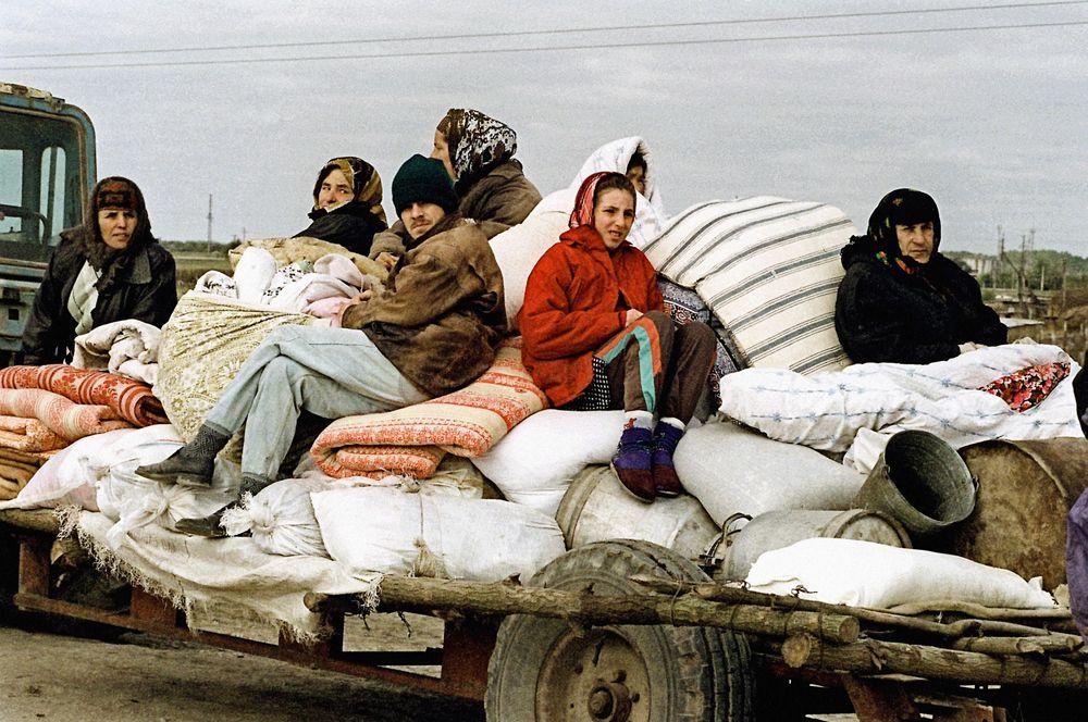 Российские войска начали массированные бомбардировки Грозного и его окрестностей, 30 сентября они вошли на территорию Чечни. На фото: жители села Знаменское Надтеречного района Чечни, находящегося в зоне боевых действий, покидают свои дома в октябре 1999 года.