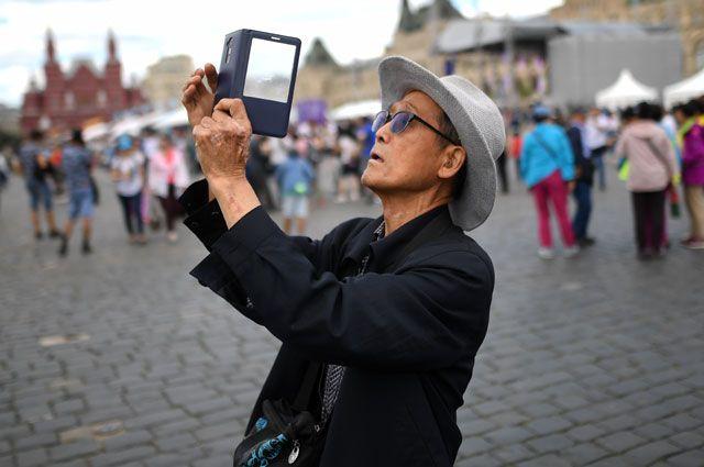 Китайские туристы фотографируются на Красной площади.