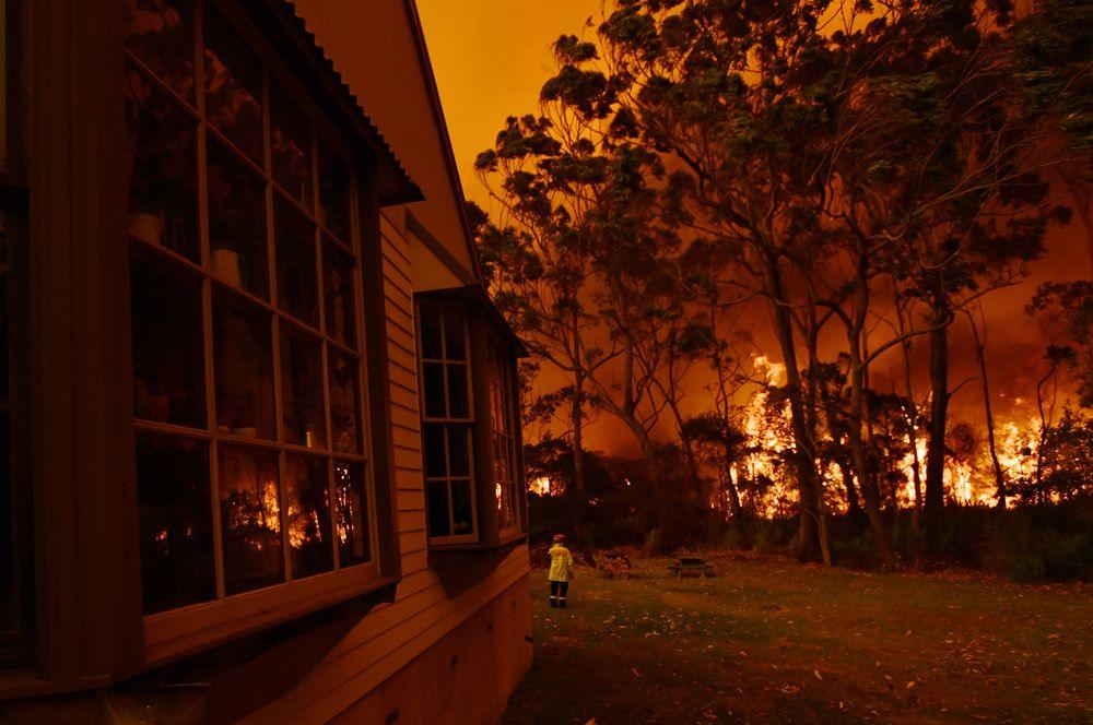 Пожарные борются с лесным пожаром около озера Табури на побережье Нового Южного Уэльса.