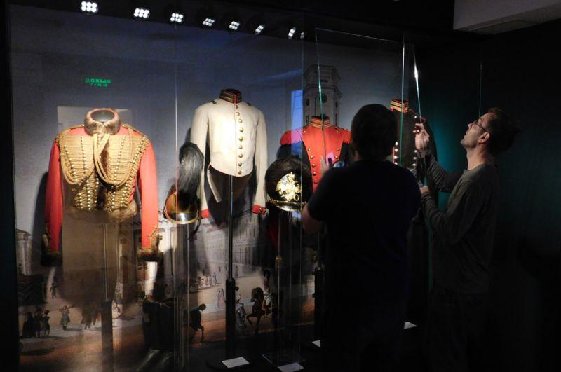 Мундиры времён Николая I. Сотрудники музея устанавливают последнее витринное стекло.