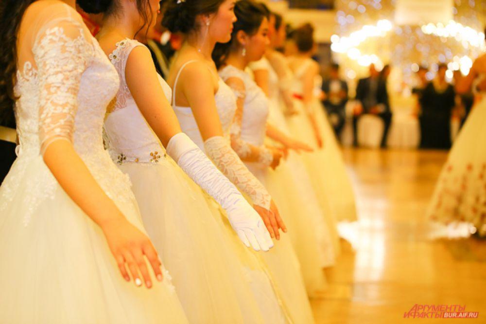 Обворожительные девушки были одеты в белые платья до пола. Некоторые из них дополняли образ диадемами, удлинёнными перчатками и изящными украшениями.