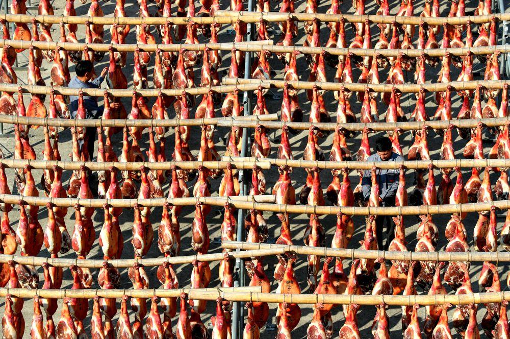 Рабочие на фабрике по производству ветчины в Цзиньхуа, Китай.